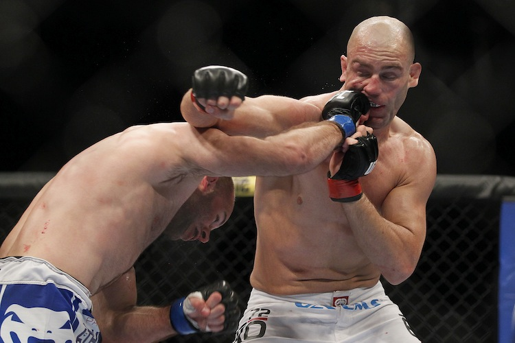 Welterweight Kenny Robertson (left) lands a right hook on Sean Pierson. (John Woods / The Canadian Press)