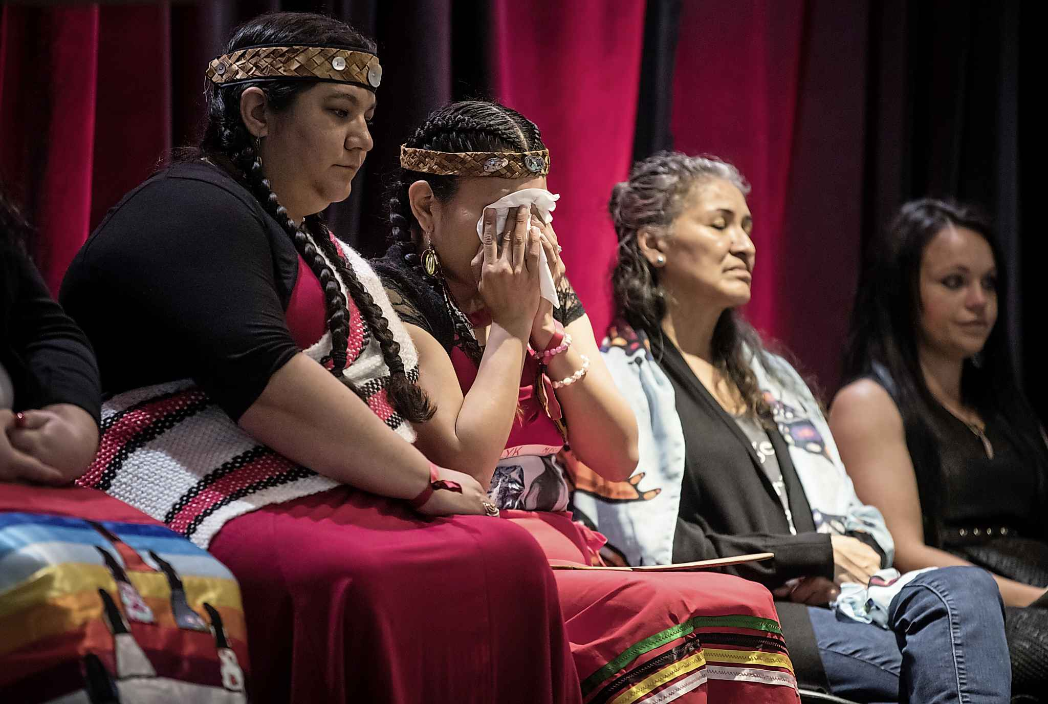 Lorelei Williams (second left) whose cousin Tanya Holyk was murdered by serial killer Robert Pickton and whose aunt Belinda Williams went missing in 1978, wipes away tears while seated with Rhiannon Bennett (from left), Sophie Merasty and Summer Rain Bentham at the released of the report on the National Inquiry into Missing and Murdered Indigenous Women and Girls. (Darryl Dyck / The Canadian Press files)