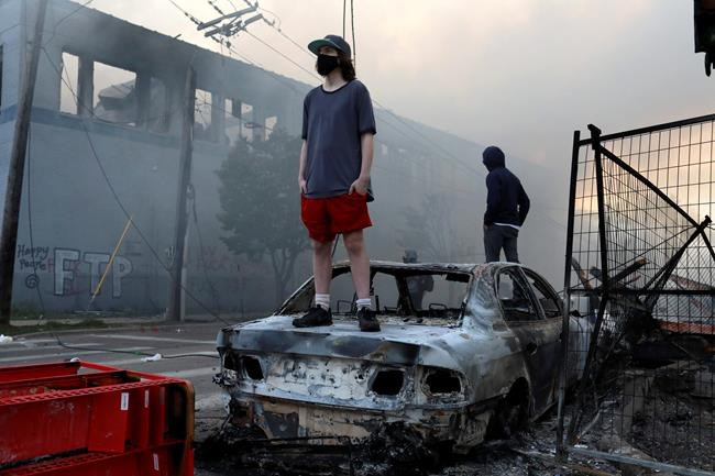 People stand on a burned up car as fires burn near a Target Store after a night of unrest and protests in the death of George Floyd early Thursday, May 28, 2020 in downtown Minneapolis. Floyd died after being restrained by Minneapolis police officers on Memorial Day. A video taken by a bystander shows a Minneapolis police officer with his knee on the neck of a man in custody who later died. The four officers involved have been fired. (David Joles/Star Tribune via AP)