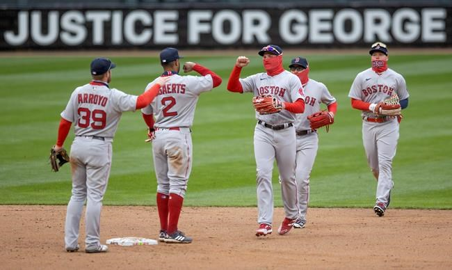 Boston Red Sox celebrate a 4-2 win over the Minnesota Twins in a baseball game Tuesday, April 13, 2021, at Target Field in Minneapolis. In the background is a sign about George Floyd. (Elizabeth Flores/Star Tribune via AP)