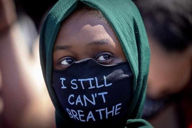 A person wears a mask Sunday, May 31, 2020, with a message at the Minneapolis corner where George Floyd was restrained by Minneapolis police. Floyd died May 25 after he was pinned at the neck by a Minneapolis police officer. (Elizabeth Flores/Star Tribune via AP)