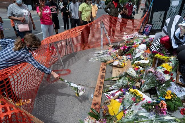 People leave flowers at a makeshift memorial, Wednesday, May 27, 2020, in Minneapolis, near the site where George Floyd, a black man who was taken into police custody on Monday and later died. (Jerry Holt/Star Tribune via AP)