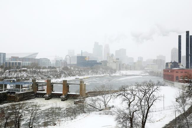 Snow flurries blow in the wind seen from the I-35W Saint Anthony Falls Bridge over the Mississippi River in Minneapolis Saturday, April 14, 2018. The National Weather Service predicts 9 to 15 inches of snow across a large swath of southern Minnesota including the Twin Cities before it's all over. (Anthony Souffle/Star Tribune via AP)