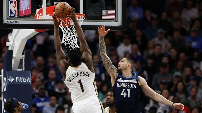 New Orleans Pelicans' Zion Williamson scores against Minnesota Timberwolves' Juancho Hernangomez in the first half of an NBA basketball game, Sunday, March 8, 2020, in Minneapolis. (AP Photo/Stacy Bengs)