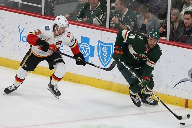Minnesota Wild's Jordan Greenway and Calgary Flames' Sean Monahan go after the puck in the first period of an NHL hockey game Monday Dec. 23, 2019, in St. Paul, Minn. (AP Photo/Stacy Bengs)