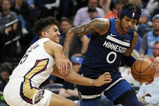 Minnesota Timberwolves' D'Angelo Russell, right, handles the ball around the defense of New Orleans Pelicans' Frank Jackson in the first half of an NBA basketball game Sunday, March 8, 2020, in Minneapolis. (AP Photo/Stacy Bengs)