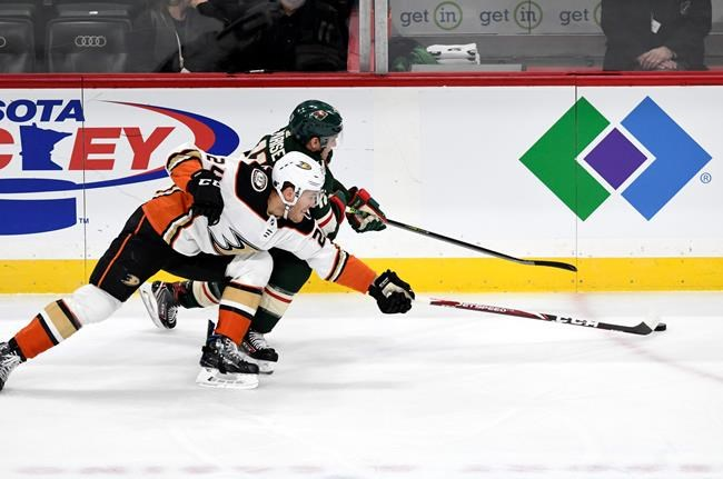 Minnesota Wild's Zach Parise, back, and Anaheim Ducks' Carter Rowney, front, go after the puck in the first period of an NHL hockey game, Tuesday, Dec. 10, 2019, in St. Paul, Minn. (AP Photo/Tom Olmscheid)