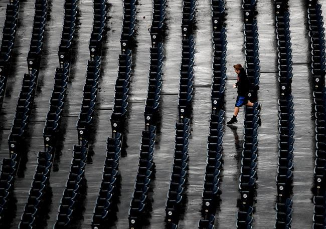 A young fan runs to his seat after a storm dumped rain on Kauffman Stadium before a baseball game between the Kansas City Royals and the Los Angeles Angels, Friday, April 13, 2018, in Kansas City, Mo. (AP Photo/Charlie Riedel)