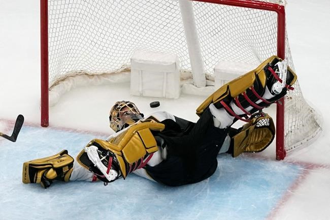 Vegas Golden Knights goaltender Marc-Andre Fleury slips as a puck flies by during the third period of an NHL hockey game against the St. Louis Blues Wednesday, April 7, 2021, in St. Louis. (AP Photo/Jeff Roberson)