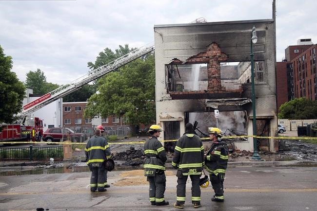 Firefighters stand as an aerial hose sends water on hot spots of a building destroyed near the Minneapolis Police Third Precinct Thursday, May 28, 2020, in Minneapolis, after a night of rioting and looting as protests continue over the death of George Floyd, who was seen on video gasping for breath during an arrest in which an officer kneeled on his neck. (AP Photo/Jim Mone)
