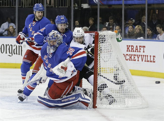 New York Rangers goalie Henrik Lundqvist (30) and Pittsburgh Penguins' Maxim Lapierre (40) fight for position during the third period of Game 5 in the first round of the NHL hockey Stanley Cup playoffs, Friday, April 24, 2015, in New York. The Rangers won 2-1. (AP Photo/Frank Franklin II)