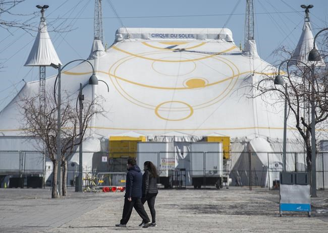 A man and woman walk by the Cirque du Soleil Big Top in Montreal's Old Port, Saturday, March 21, 2020, as COVID-19 cases rise in Canada and around the world. THE CANADIAN PRESS/Graham Hughes