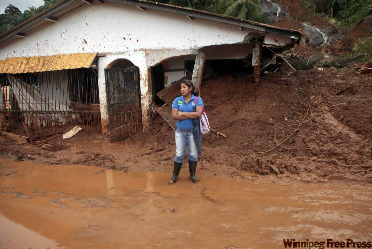 A woman stands in front of a house partially covered by mud after a mudslide in Portobelo, northern Panama on Friday. A landslide due to  heavy rains killed at least eight people on Wednesday.