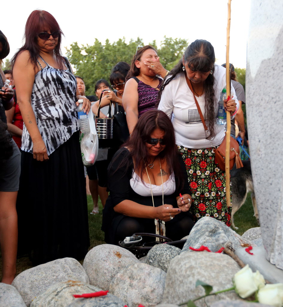 Tina Fontaine places a  tobacco offering in honour of her daughter Tina Fontaine during a vigil for her and Faron Hall at the Oodena Circle at The Forks Tuesday night.