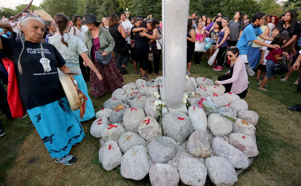 People place  tobacco offerings at a vigil for Tina Fontaine and Faron Hall at the Alexander Docks.