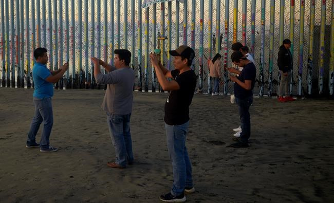 People record with their phones in front of the border wall Thursday, Jan. 10, 2019, along the beach in Tijuana, Mexico. Taking the shutdown fight to the Mexican border, U.S. President Donald Trump edged closer Thursday to declaring a national emergency in an extraordinary end run around Congress to fund his long-promised border wall. (AP Photo/Gregory Bull)