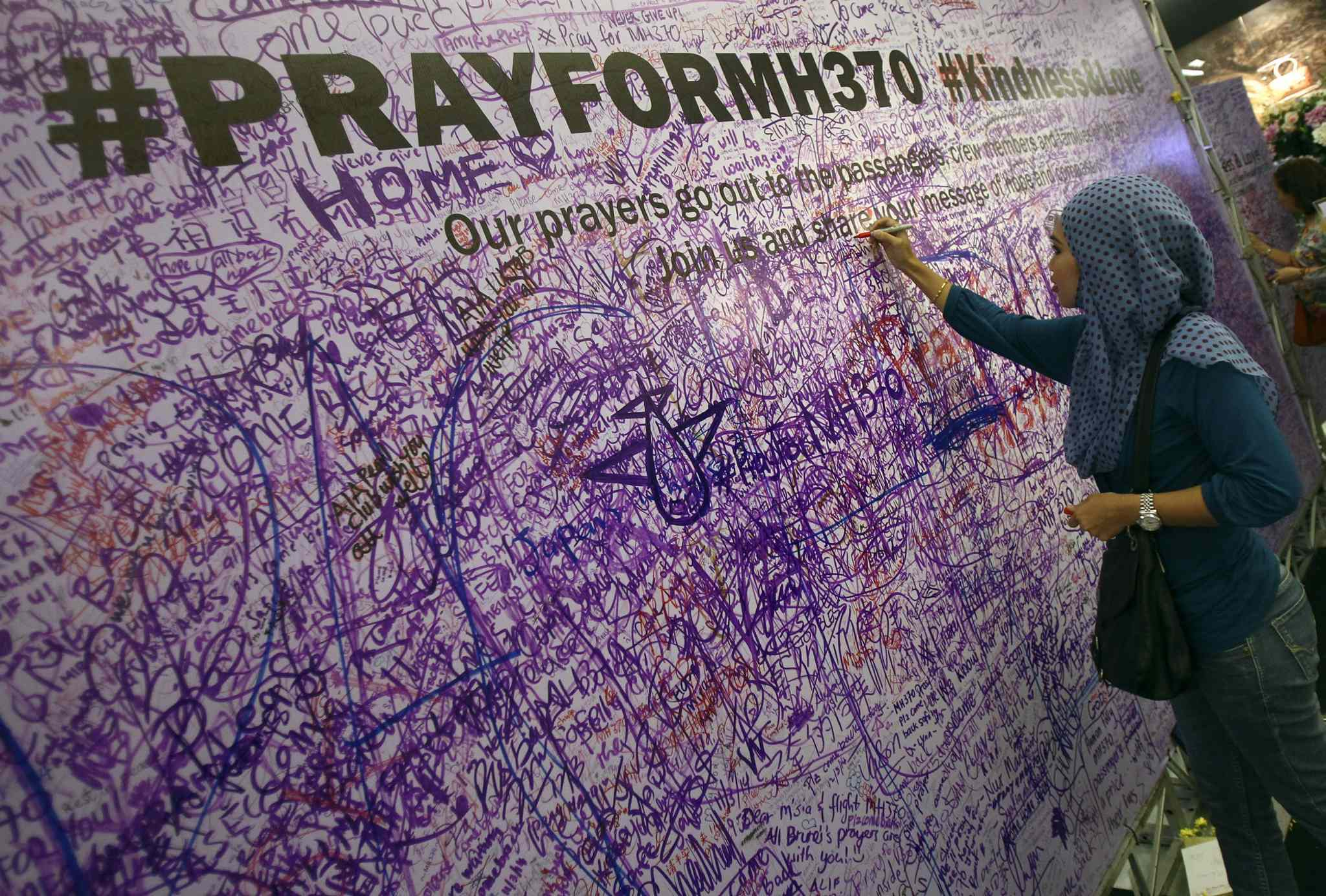 A woman leaves a message for passengers aboard a missing Malaysia Airlines plane, at a shopping mall in Petaling Jaya, near Kuala Lumpur, Malaysia, Sunday, March 16, 2014. Malaysian authorities Sunday were investigating the pilots of the missing jetliner after it was established that whoever flew off with the Boeing 777 had intimate knowledge of the cockpit and knew how to avoid detection when navigating around Asia.