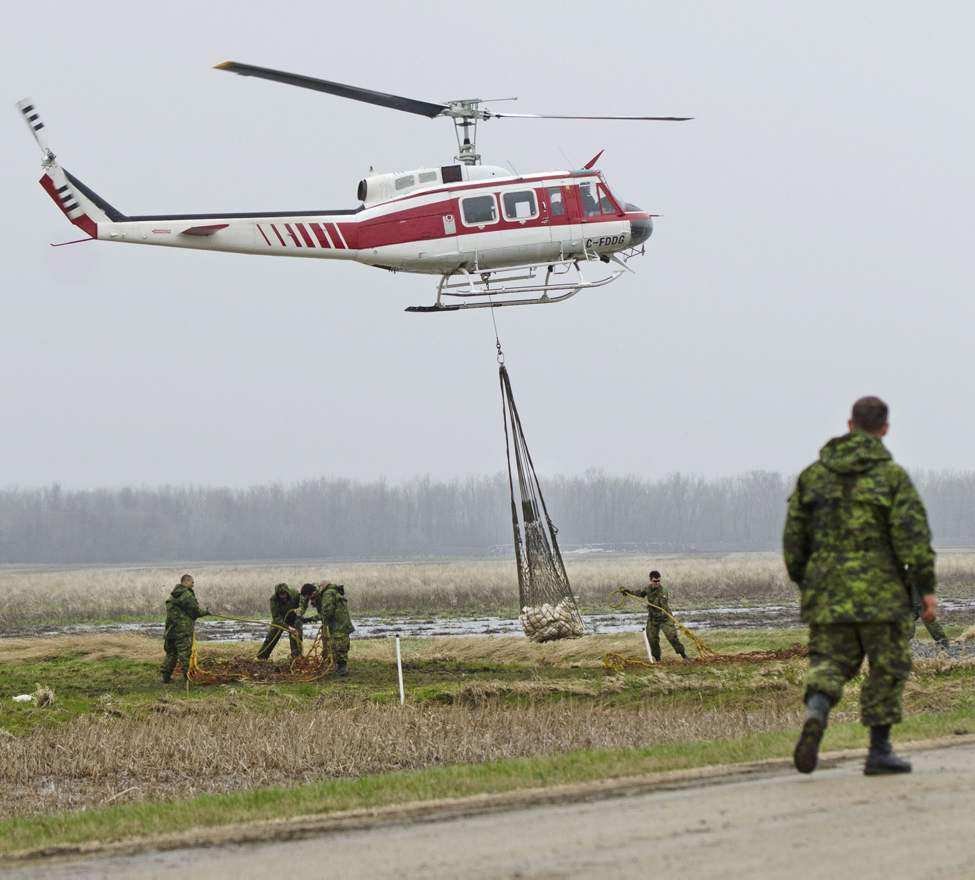 Soldiers from the 2nd Battalion, Princess Patricia's Canadian Light Infantry (2 PPCLI) help load sandbags to be airlifted to the front lines of the fight against the rising Assiniboine River near Portage La Prairie, Manitoba Tuesday May 10, 2011. Helicopters have to be used to transport sandbags, as it was difficult for trucks to drive to the dikes. (THE CANADIAN PRESS/David Lipnowski) (CP)