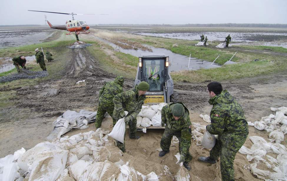 Soldiers from the 2nd Battalion, Princess Patricia's Canadian Light Infantry (2 PPCLI) help load sandbags to be airlifted to the front lines of the fight against the rising Assiniboine River near Portage La Prairie, Manitoba Tuesday May 10, 2011. Helicopters have to be used to transport sandbags, as it was difficult for trucks to drive to the dikes. (THE CANADIAN PRESS/David Lipnowski)
