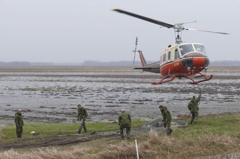 Soldiers from the 2nd Battalion, Princess Patricia's Canadian Light Infantry (2 PPCLI) help load sandbags to be airlifted to the front lines of the fight against the rising Assiniboine River near Portage La Prairie, Manitoba Tuesday May 10, 2011. Helicopters had to be used to transport sandbags, as it was difficult for trucks to drive to the dikes. THE CANADIAN PRESS/David Lipnowski (CP)