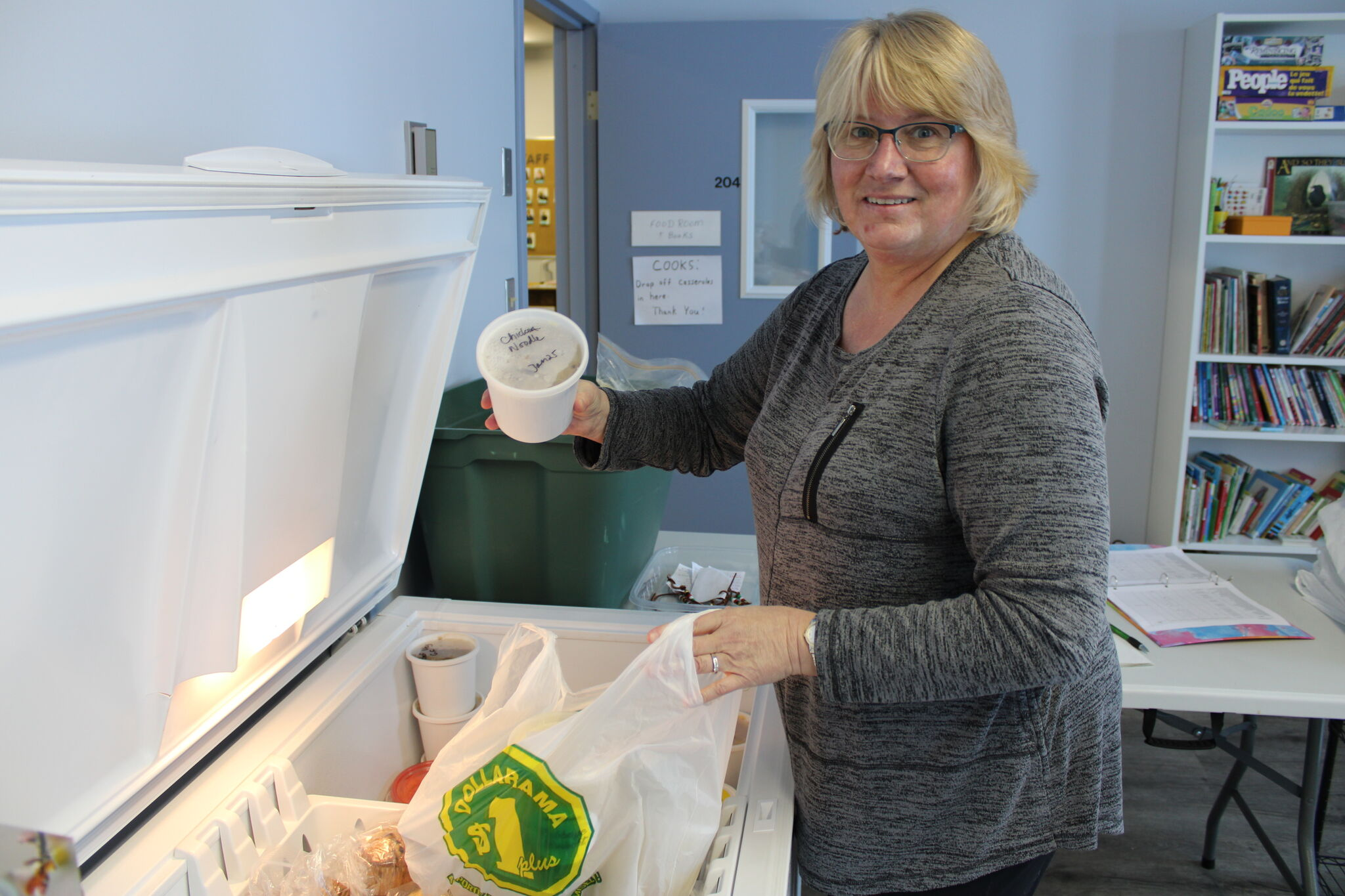 Tammy Bekkering fills a hamper at Steinbach Community Outreach. While she is maskless for the photo, she always wears a mask for safety when she's making them for clients.