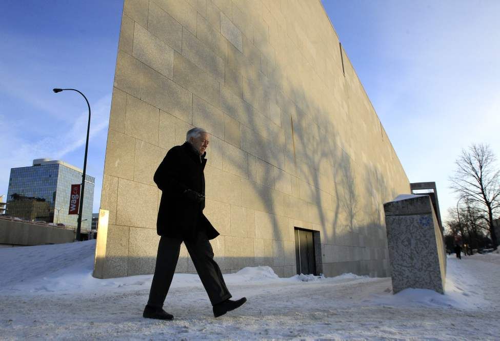 A pedestrian walks past the WAG building which is catching late afternoon shadows of trees in downtown Winnipeg. January 11, 2011