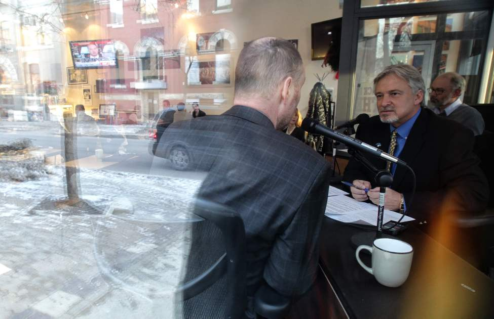 The Exchange District is reflected in the window of the Winnipeg Free Press News Caf� while John Harris president and CEO of Prairie Public Broadcasting (right) interviews Free Press City Editor Paul Samyn for a live segment on PBS radio at the Caf�. Some of his other guests were Colin Ferguson president of Travel Manitoba and Mayor Sam Katz. December 9, 2011