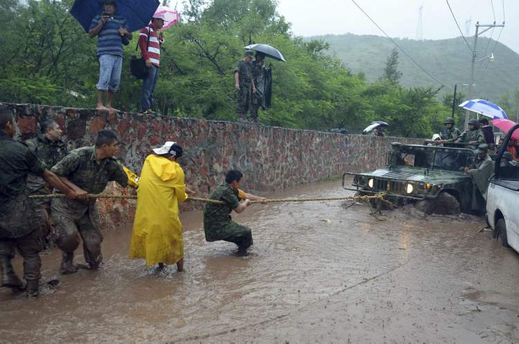 Army soldiers work to try to get their vehicle out of a flooded portion of a road caused by Tropical Storm Manuel in the city of Chilpancingo, Mexico, Sunday Sept. 15, 2013. (AP Photo/Alejandrino Gonzalez) (CP)