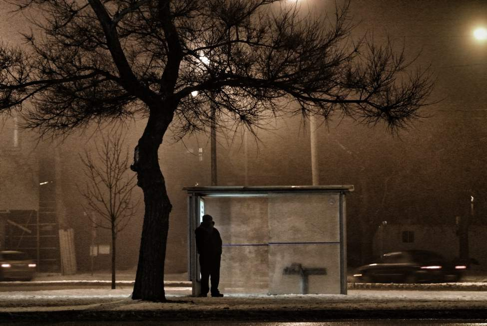 A person waits at a bus shelter on Portage Avenue Wednesday evening as temperatures reached -11 C overnight. Wednesday, February 1, 2012. (MIKE DEAL / WINNIPEG FREE PRESS)