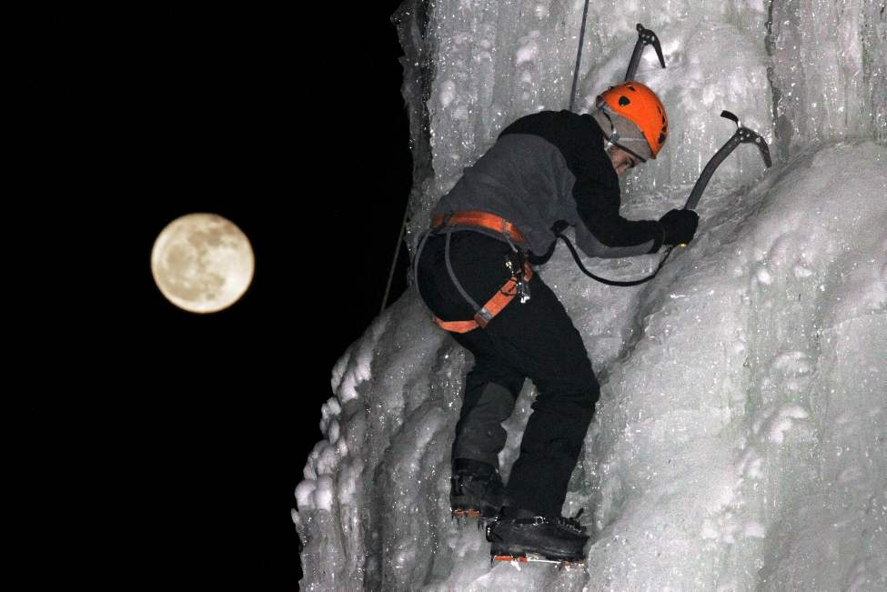 Nicolas Baisburd of the Alpine Club of Canada – St. Boniface section climbs the ice tower close to Fort Gibraltar as the moon rises in the distance. Wednesday, February 08, 2012. (MIKE DEAL / WINNIPEG FREE PRESS)
