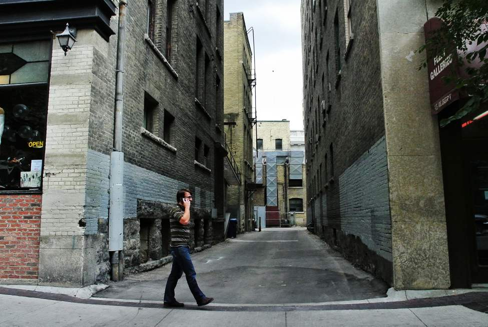 A Pedestrian uses his cell phone in Winnipeg's Exchange district.  Thursday, September 13, 2012.  (MIKE DEAL / WINNIPEG FREE PRESS)