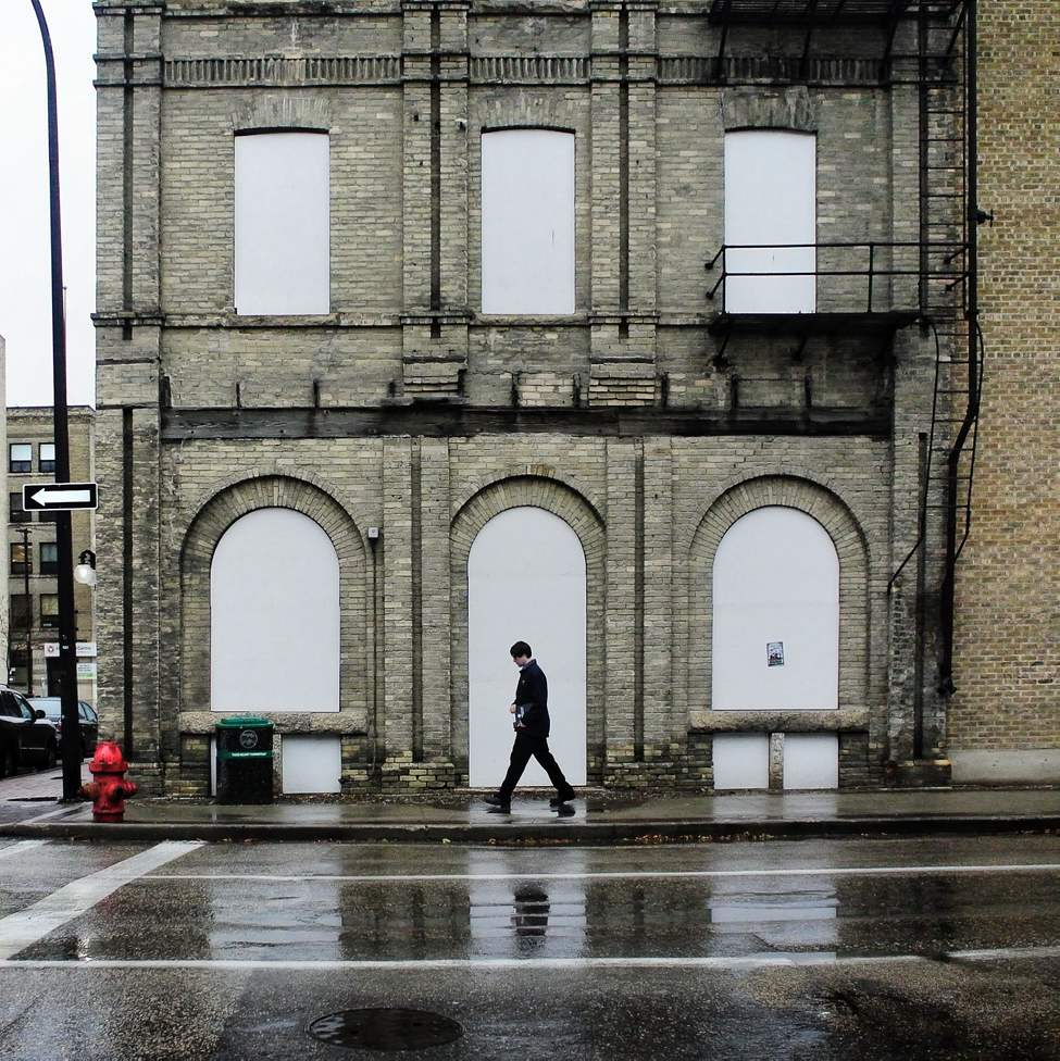 A pedestrian walks the wet streets of the Exchange District in Winnipeg's Downtown.   Tuesday, October 23, 2012.  (MIKE DEAL / WINNIPEG FREE PRESS)