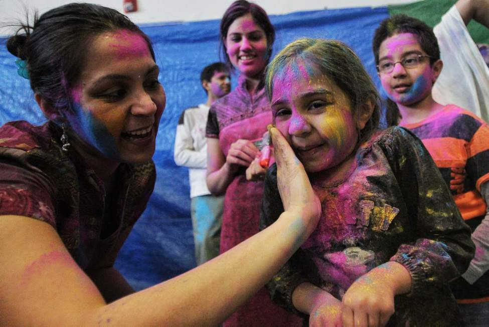 Shweta Banthia and her daughter Van, 4, observe Holi, a religious spring festival celebrated by Hindus as a festival of colours at the Dr. Raj Pandey Hindu Centre Sunday afternoon. March 30, 2013 (Mike Deal / Winnipeg Free Press)