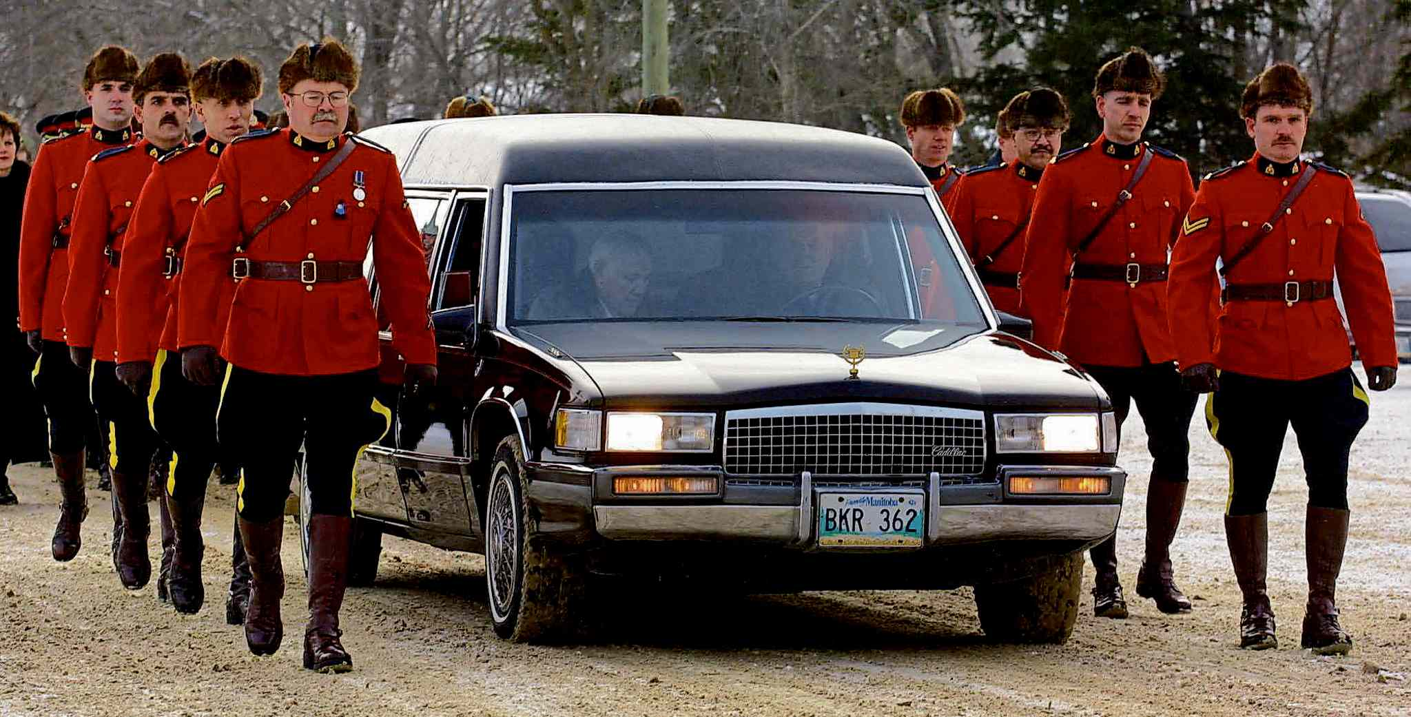 The hearse containing the casket of RCMP Constable Dennis Strongquill is escorted by some of the over 300 police officers who came to the church in Powerview, Man. for his memorial service on Thursday, Dec. 27, 2001.