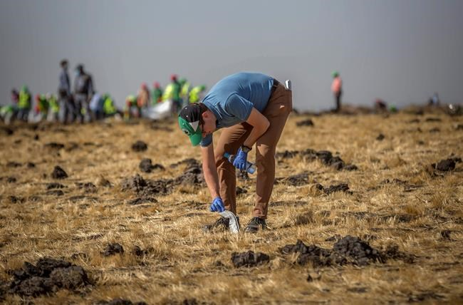A foreign investigator examines wreckage at the scene where the Ethiopian Airlines Boeing 737 Max 8 crashed shortly after takeoff on Sunday killing all 157 on board, near Bishoftu, or Debre Zeit, south of Addis Ababa, in Ethiopia Tuesday, March 12, 2019. Ethiopian Airlines had issued no new updates on the crash as of late afternoon Tuesday as families around the world waited for answers, while a global team of investigators began picking through the rural crash site. (AP Photo/Mulugeta Ayene)