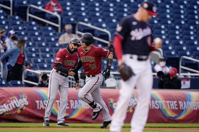 Arizona Diamondbacks' Carson Kelly, center, runs the bases on a solo home run as Washington Nationals starting pitcher Patrick Corbin, right, stands on the mound during the first inning of a baseball game at Nationals Park, Thursday, April 15, 2021, in Washington. (AP Photo/Alex Brandon)