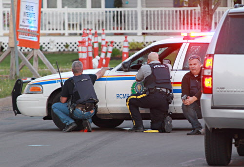 Police officers take cover behind their vehicles in Moncton, N.B. on Wednesday June 3, 2014. The RCMP says three of its officers were killed in Moncton, N.B., by a man armed with guns and two other officers were injured as the Mounties conducted a manhunt across the city's north end on Wednesday night for the shooter.