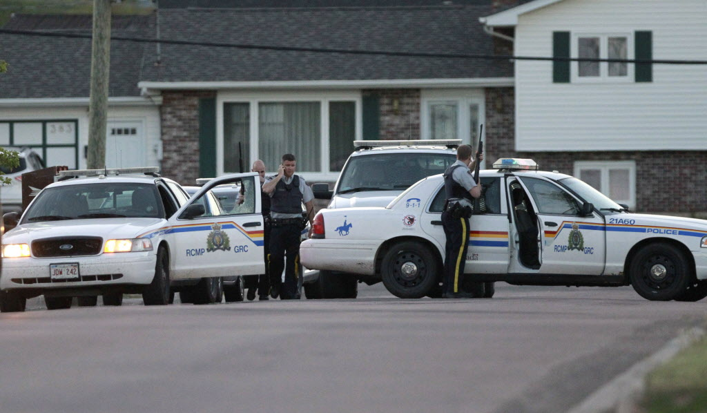 Codiac RCMP officers take cover behind their vehicles on Penrose Street in Moncton, N.B. on Wednesday June 4.  (Moncton Times & Transcript-Ron Ward / THE CANADIAN PRESS)