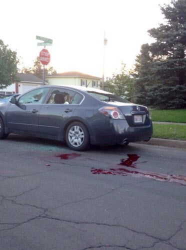 A car sits on a road with it's windows shot out and blood on the ground in Moncton, N.B. on Wednesday.