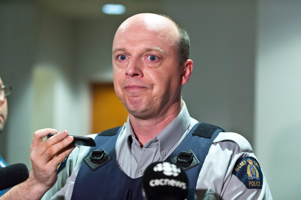 RCMP officer Damien Theriault holds back tears while addressing the media during a press conference at City Hall in Moncton.  (Marc Grandmaison / THE CANADIAN PRESS )