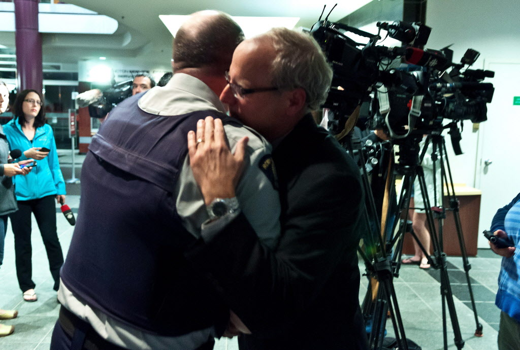 RCMP officer Damien Theriault, left, and Mayor George LeBlanc hug after addressing the media during a late press conference at City Hall in Moncton, N.B.on Wednesday.  (Marc Grandmaison / THE CANADIAN PRESS )