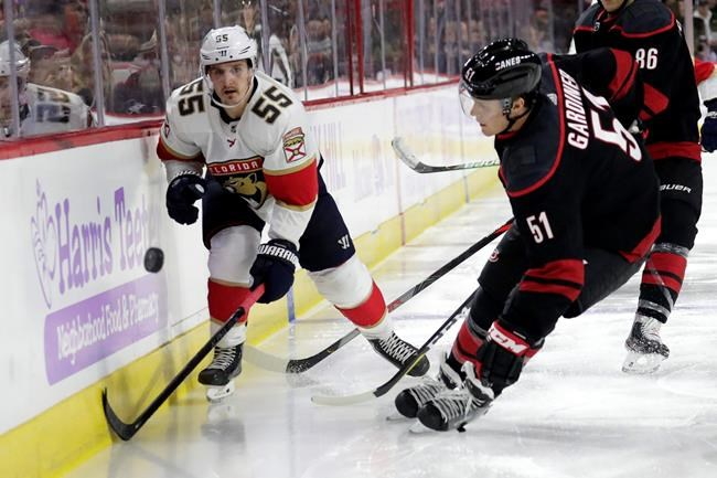 Florida Panthers' Noel Acciari (55) and Carolina Hurricanes' Jake Gardiner (51) go for the puck during the third period of an NHL hockey game against the Florida Panthers in Raleigh, N.C., Saturday, Nov. 23, 2019. (AP Photo/Chris Seward)