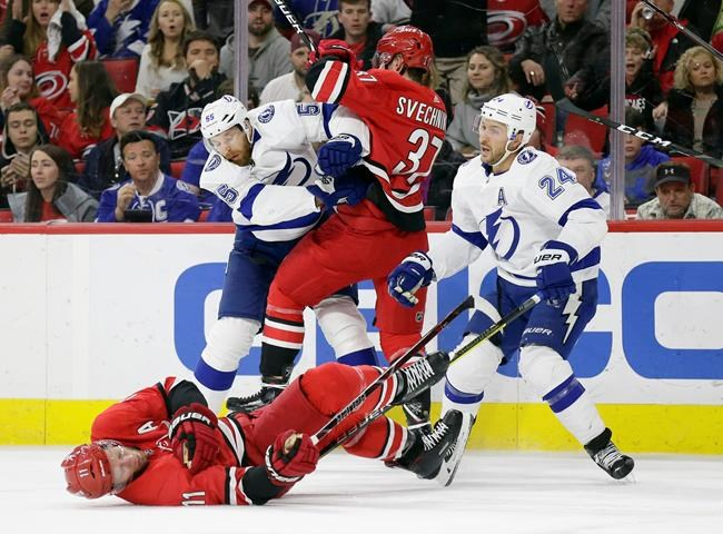 Carolina Hurricanes' Jordan Staal (11) falls to the ice with an injury as Andrei Svechnikov (37), of Russia, struggles with Tampa Bay Lightning's Braydon Coburn (55) and Ryan Callahan (24) during the first period of an NHL hockey game in Raleigh, N.C., Thursday, March 21, 2019. (AP Photo/Gerry Broome)