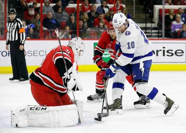 Carolina Hurricanes goalie Curtis McElhinney (35) and Jaccob Slavin defend while Tampa Bay Lightning's J.T. Miller (10) tries to score during the second period of an NHL hockey game in Raleigh, N.C., Thursday, March 21, 2019. (AP Photo/Gerry Broome)