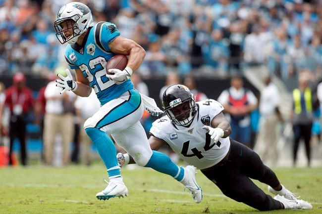 Carolina Panthers running back Christian McCaffrey (22) runs for a tuchdown as Jacksonville Jaguars middle linebacker Myles Jack (44) reaches during the first half of an NFL football game in Charlotte, N.C., Sunday, Oct. 6, 2019. (AP Photo/Brian Blanco)