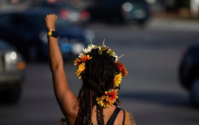 SeaSea Stark, of Omaha, raises her fist as protesters gather at 72nd and Dodge in Omaha on Monday, Aug. 24, 2020. The protest was organized in response to the shooting of Jacob Blake, a Black man in Wisconsin, who was shot multiple times in the back by police on Sunday. (Anna Reed/Omaha World-Herald via AP)