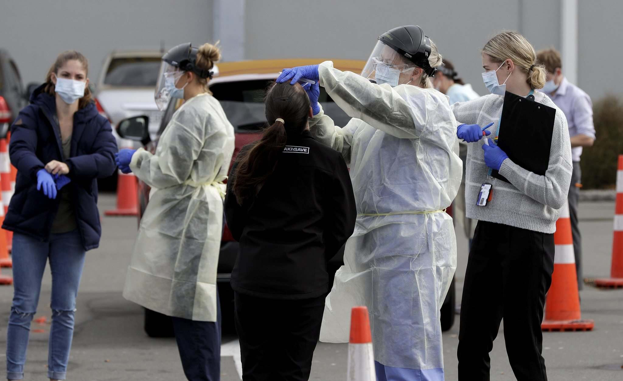 In April 2020, medical staff tested shoppers who volunteered at a pop-up community COVID-19 testing station at a supermarket carpark in Christchurch, New Zealand. (Mark Baker / The Associated Press files)