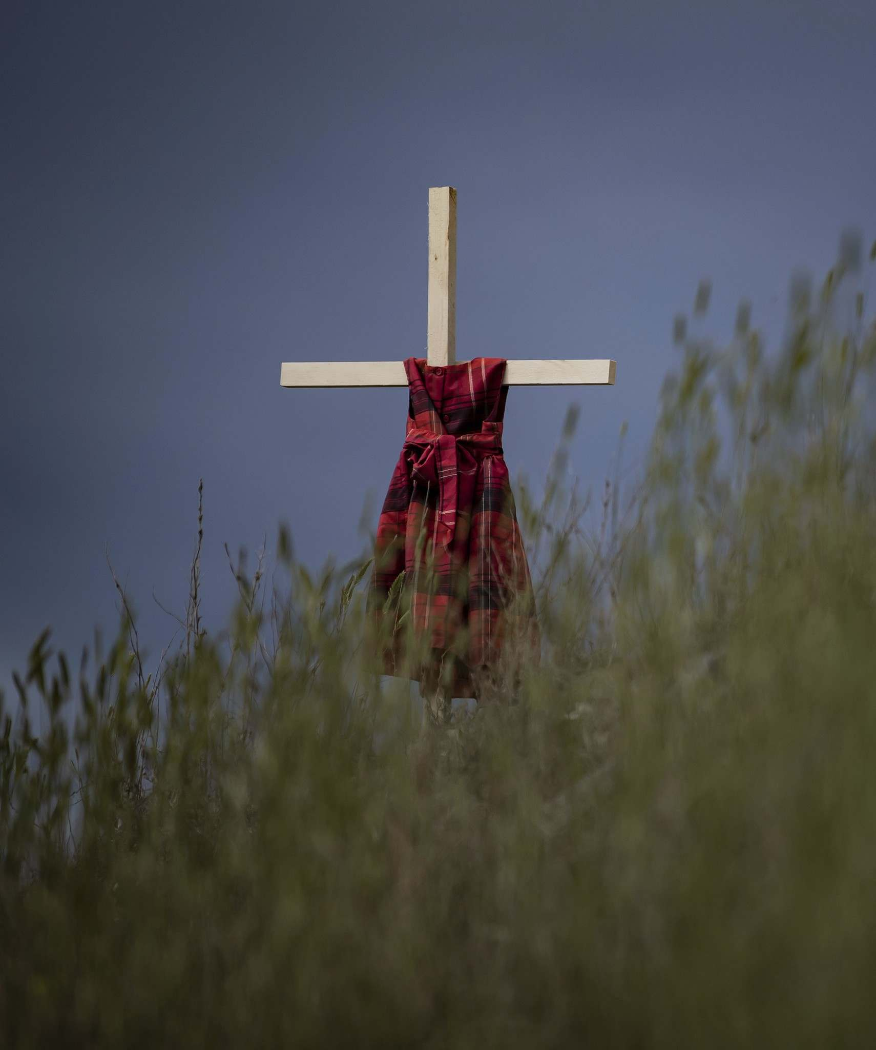 A child's dress hangs on a cross in the wind near the former Kamloops Indian Residential School, to honour the 215 children whose remains have been discovered buried near the facility. (Darryl Dyck/ The Canadian Press)