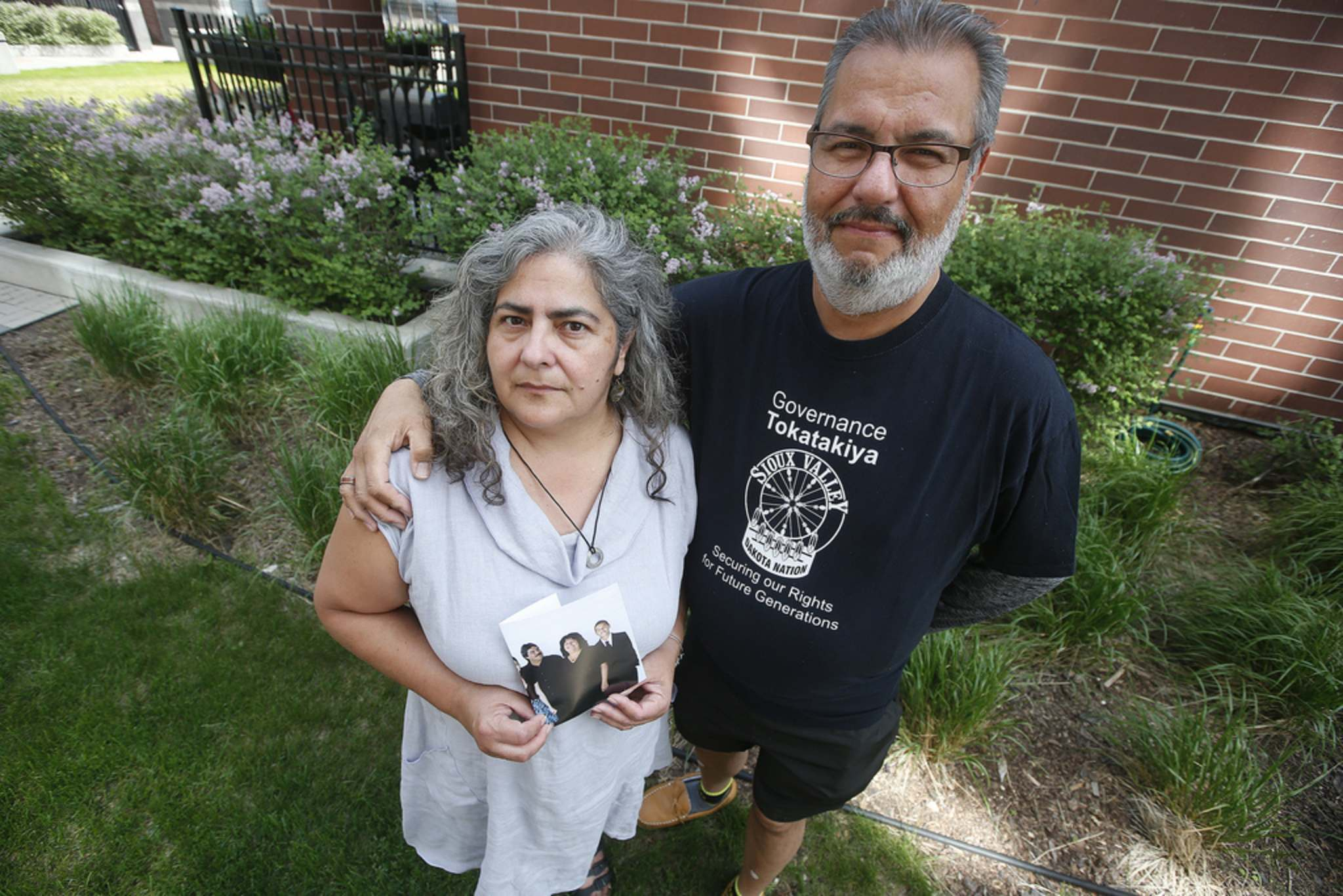 <p>James and Tannis Bullard hold a photo of their sister Kim Bullard who died June 1 of COVID-19 after she was transported out of Manitoba to a hospital in London, Ont.</p>