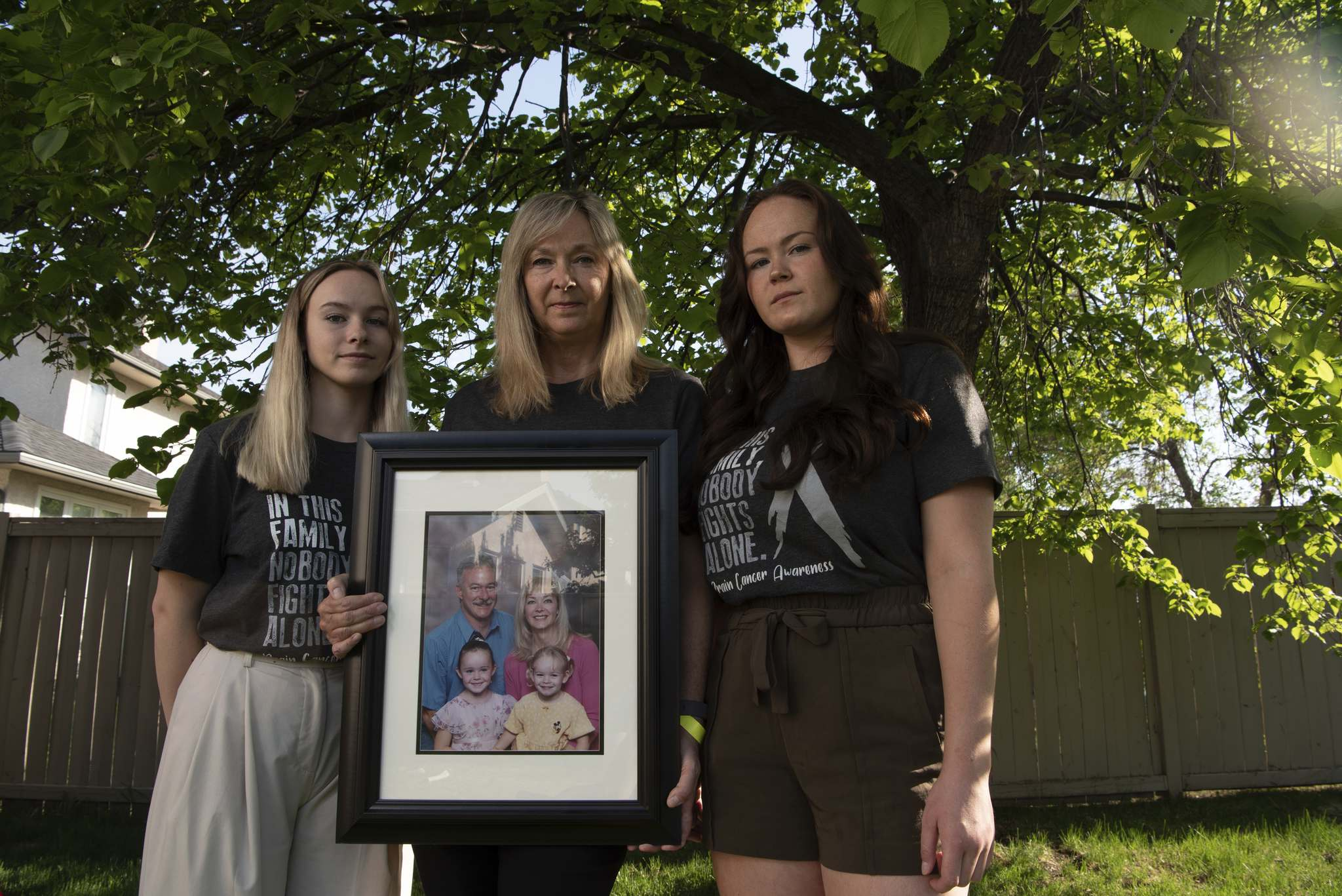ALEX LUPUL / WINNIPEG FREE PRESS FILES Jo-Anne McNeil holds a family photo with her daughters Sarah and Taylor at their home in Winnipeg. </p>